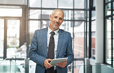 Buy stock photo Portrait of a mature businessman working on a digital tablet in a modern office