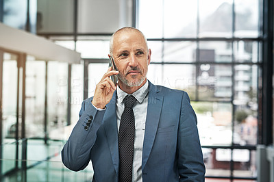 Buy stock photo Cropped shot of a mature businessman talking on a cellphone in a modern office