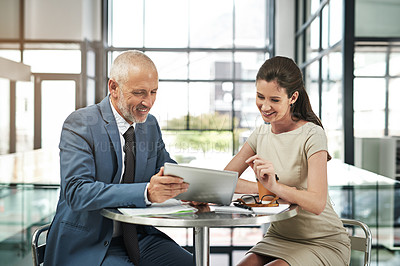 Buy stock photo Cropped shot of two businesspeople working together on a digital tablet in a modern office
