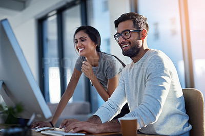 Buy stock photo Shot of two young coworkers using a computer together at work