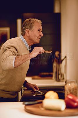 Buy stock photo Shot of an elderly man cooking a meal in his kitchen