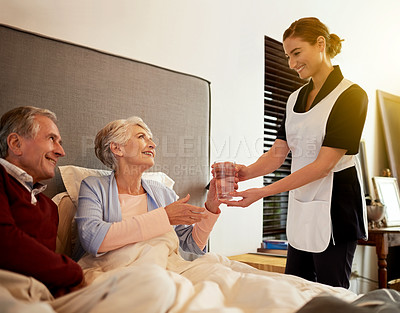 Buy stock photo Shot of a nurse assisting and elderly patient and her husband in their room