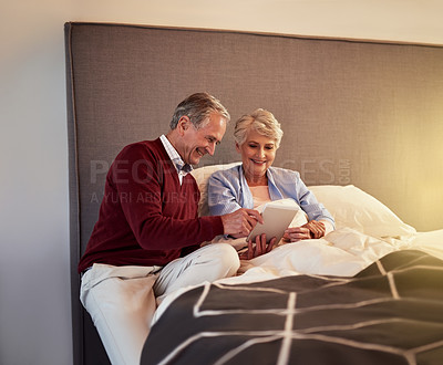 Buy stock photo Cropped shot of a senior couple looking at a tablet together while sitting in bed