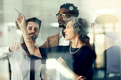 Buy stock photo Cropped shot of a group of businesspeople brainstorming with notes on a glass wall in an office