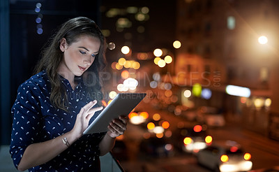 Buy stock photo Cropped shot of a young businesswoman working late on a digital tablet outside