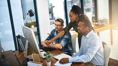 Buy stock photo Cropped shot of three businesspeople working around a computer in the office