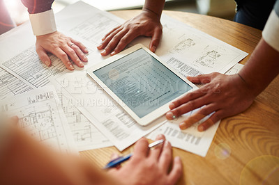 Buy stock photo Cropped shot of a group of architects looking over paper and digital blueprints
