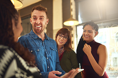Buy stock photo Shot of a group of smiling coworkers talking together over a digital tablet in an office