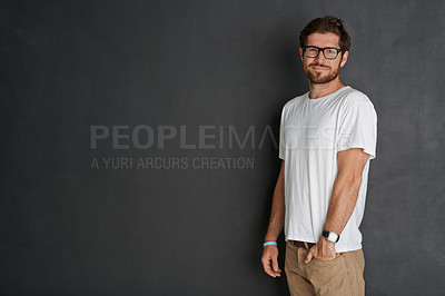 Buy stock photo Studio portrait of a young man standing with his hand in his pocket against a grey background