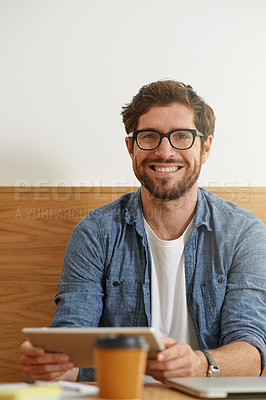 Buy stock photo Cropped portrait of a young man working on his digital tablet