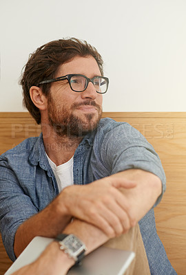 Buy stock photo Cropped shot of a thoughtful young man sitting at a table
