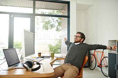Buy stock photo Shot of a young entrepreneur stretching at his work desk