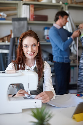 Buy stock photo Portrait of a young fashion designer sewing while a colleague works in the background