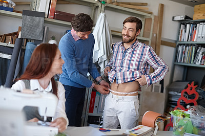 Buy stock photo Shot of a young fashion designer sewing while a colleague works with a client in the background