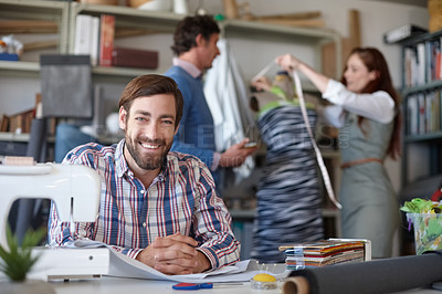 Buy stock photo Portrait of a young fashion designer sitting in the workshop while his colleagues work in the background