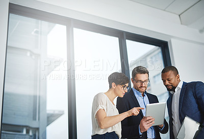 Buy stock photo Shot of a team of colleagues using a digital tablet together at work