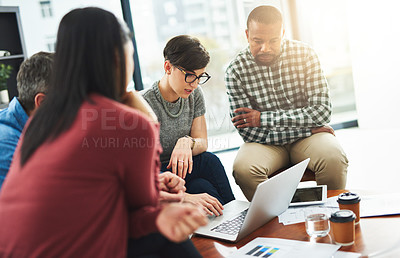 Buy stock photo Shot of a group of colleagues working together on a laptop