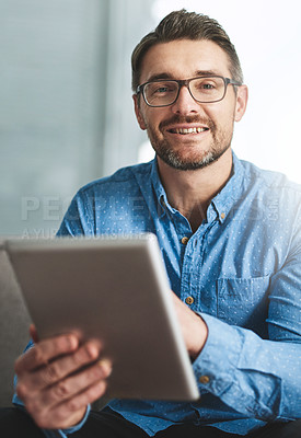 Buy stock photo Portrait of a businessman using his digital tablet while sitting on a sofa in the office