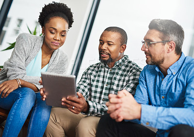 Buy stock photo Shot of a creative team discussing something on a digital tablet