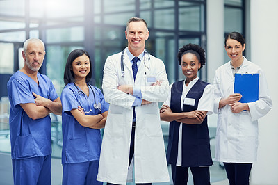 Buy stock photo Portrait of a group of smiling medical professionals standing in a hospital corridor