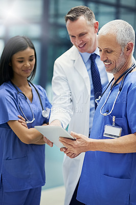 Buy stock photo Shot of a group of doctors talking together over a digital tablet while standing in a hospital