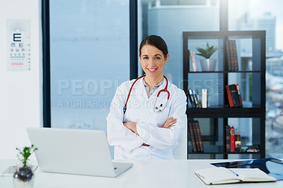 Buy stock photo Portrait of a young female doctor sitting at a desk using a laptop