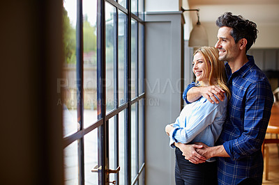 Buy stock photo Shot of a smiling young couple hugging each other in their kitchen