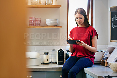 Buy stock photo Shot of a young woman sitting on her kitchen counter using a digital tablet