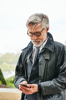 Buy stock photo Shot of a handsome mature man using a cellphone in the city