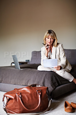 Buy stock photo Shot of a mature businesswoman sitting on a hotel bed using a laptop and reading paperwork