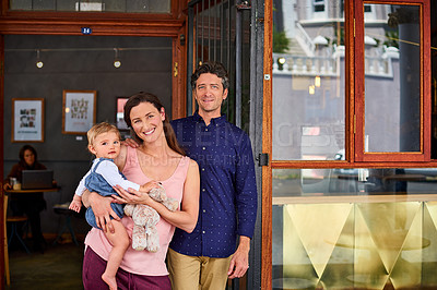 Buy stock photo Portrait of smiling couple and their little girl standing in front of their bakery
