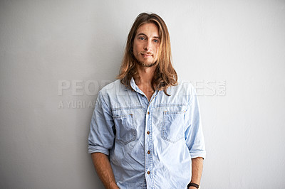 Buy stock photo Studio portrait of a young man standing with his hands in his pockets against a gray background