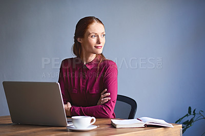 Buy stock photo Shot of a young woman deep in thought while working on a laptop in an office