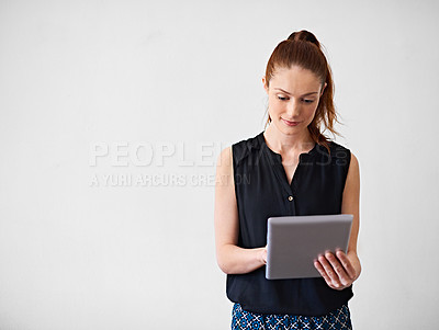 Buy stock photo Studio shot of a young woman using a digital tablet against a gray background