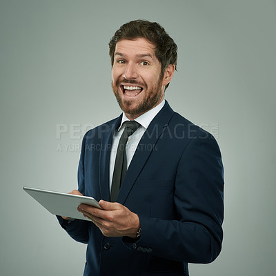 Buy stock photo Studio portrait of a corporate businessman using his digital tablet against a grey background