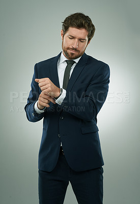 Buy stock photo Studio shot of a corporate businessman adjusting his cuffs against a grey background