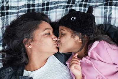 Buy stock photo Cropped shot of a little girl and her mother bonding while lying on a blanket outside together