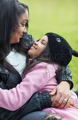 Buy stock photo Cropped shot of a mother and her young daughter bonding while sitting outside