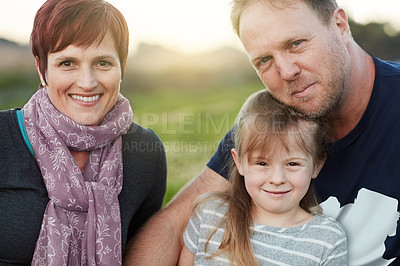 Buy stock photo Portrait of a cute little girl and her parents sitting outside together