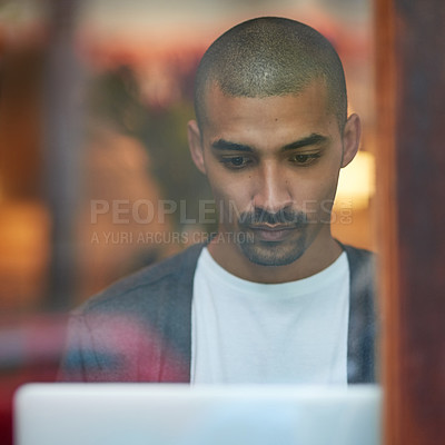 Buy stock photo Cropped shot of a young man working on his laptop in a coffee shop