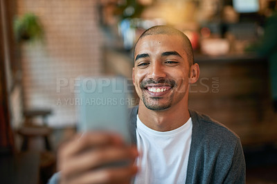 Buy stock photo Cropped shot of a young man texting on his cellphone in a cafe
