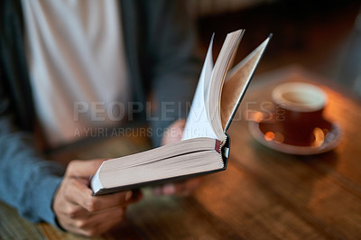 Buy stock photo Closeup shot of a young man reading a book in a cafe