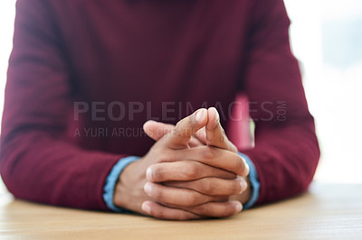 Buy stock photo Shot of an unidentifiable businessman sitting with his hands folded in the office