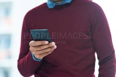 Buy stock photo Shot of an unidentifiable businessman using his smartphone in the office