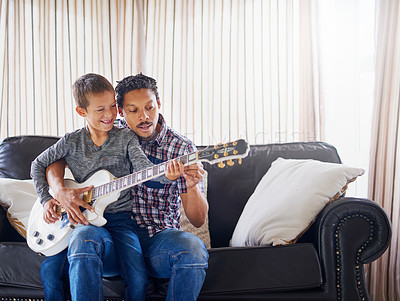 Buy stock photo Cropped shot of a father teaching his son how to play guitar at home