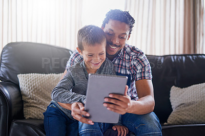 Buy stock photo Cropped shot of a father and son using a digital tablet at home