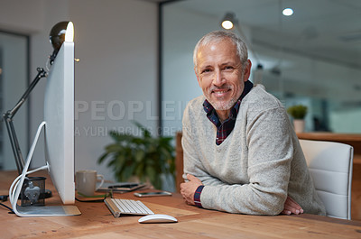 Buy stock photo Portrait of a smiling mature businessman working on a computer in an office