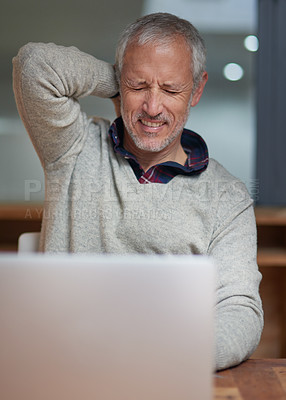 Buy stock photo Shot of a mature businessman suffering from neck pain while using a laptop in an office