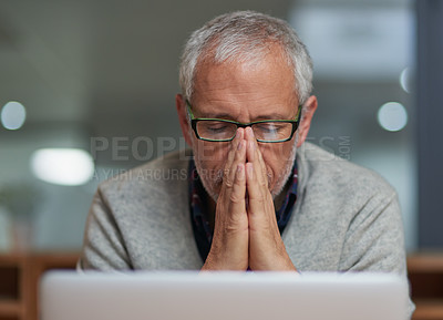 Buy stock photo Shot of a stressed out mature businessman using a laptop while working in an office