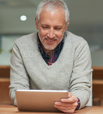 Buy stock photo Shot of a mature businessman using a digital tablet while working in an office
